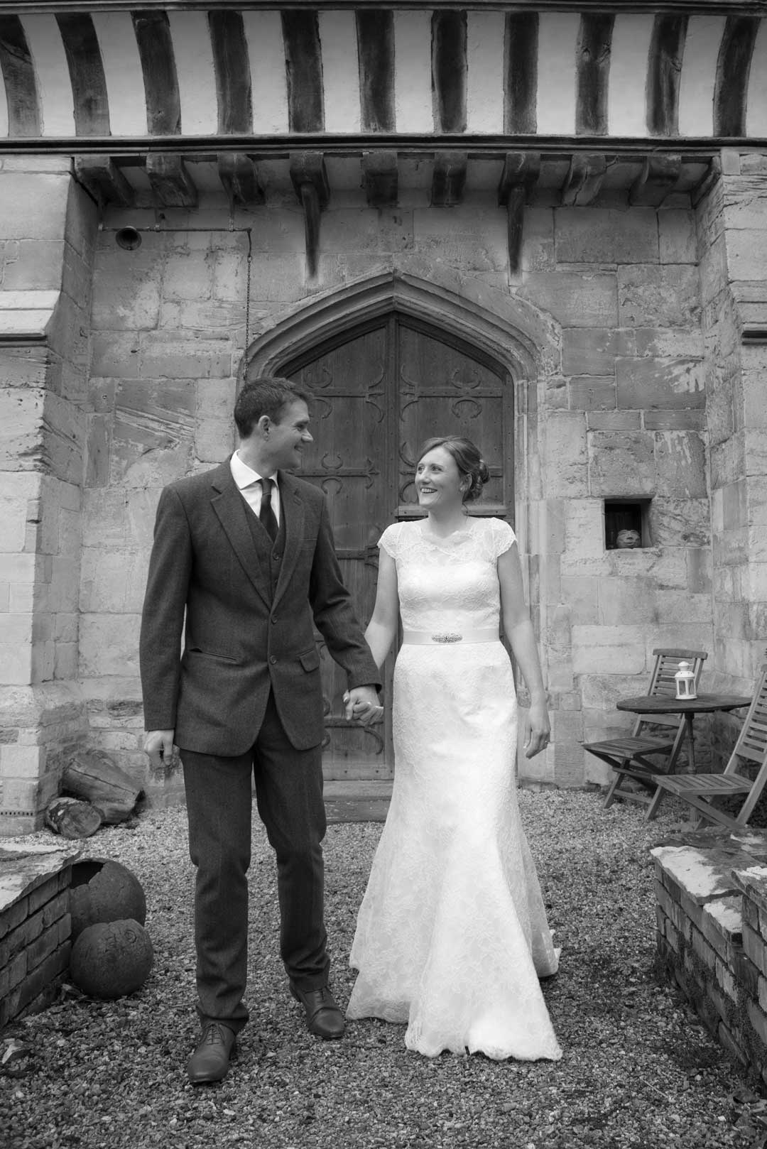 wedding couple black and white photography in front of medival building at Priors Tithe Barn in Brockworth Goucester